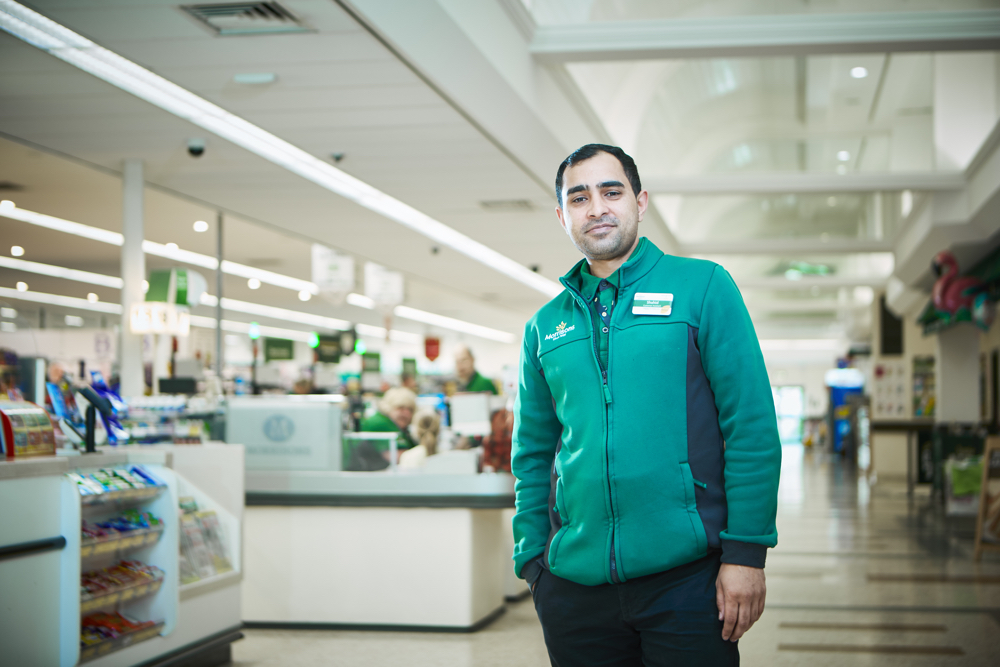 Shah, a store colleague standing within store