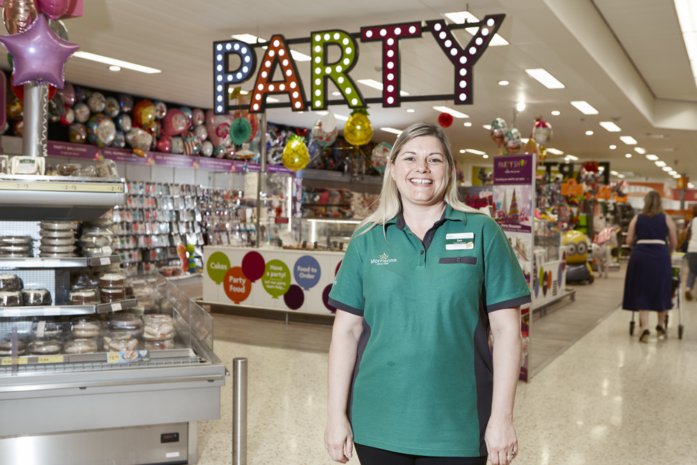 Store colleague standing in front of store Party section