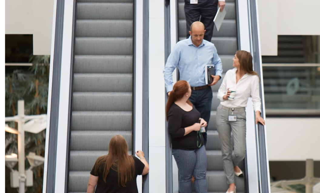 Colleagues heading down on escalator